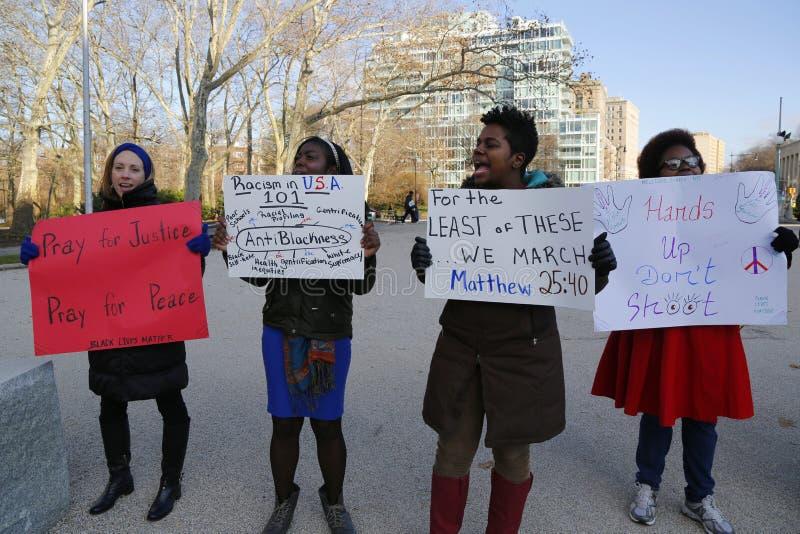 Un protestataire tient un signe pendant une marche contre la brutalité de police et la décision du grand jury sur le cas d'Eric G images libres de droits