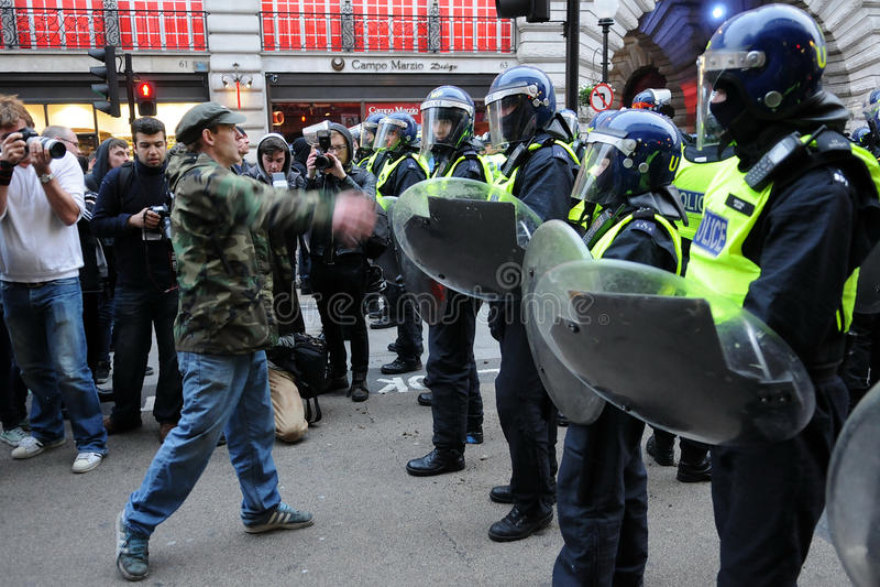 Un protestatore confronta la polizia di tumulti a Londra fotografia stock