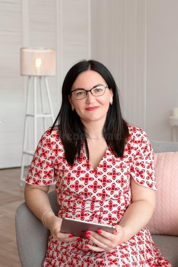Un psychologue professionnel de docteur avec des verres s'assied dans un bureau lumineux avec un comprimé dans ses mains et souri photographie stock