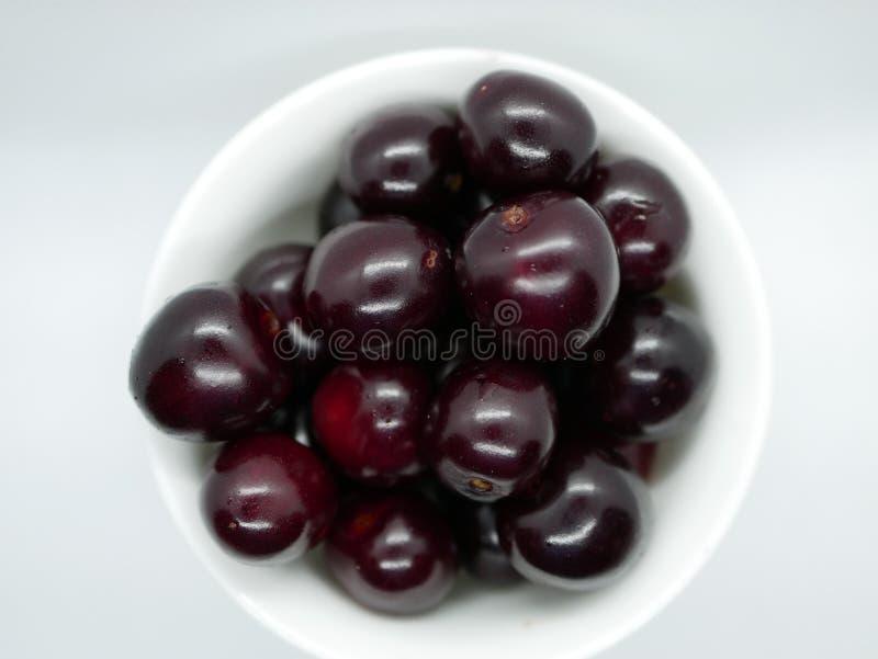 Un puñado de cerezas marrón maduras en un pequeño cuenco blanco de la porcelana en un fondo blanco vitamina natural de la cosecha foto de archivo libre de regalías