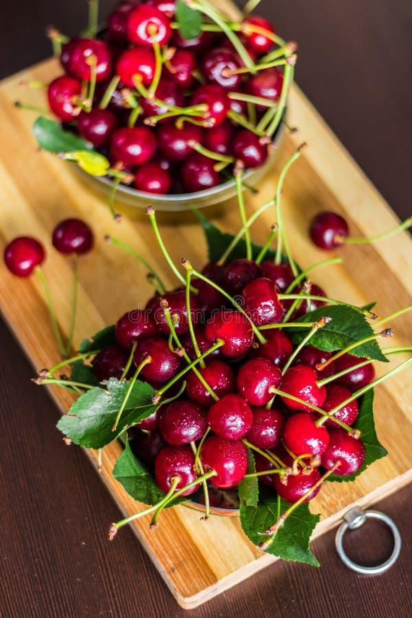 Un puñado de cerezas rojas maduras en una poder del metal en un fondo marrón con las hojas verdes imagen de archivo