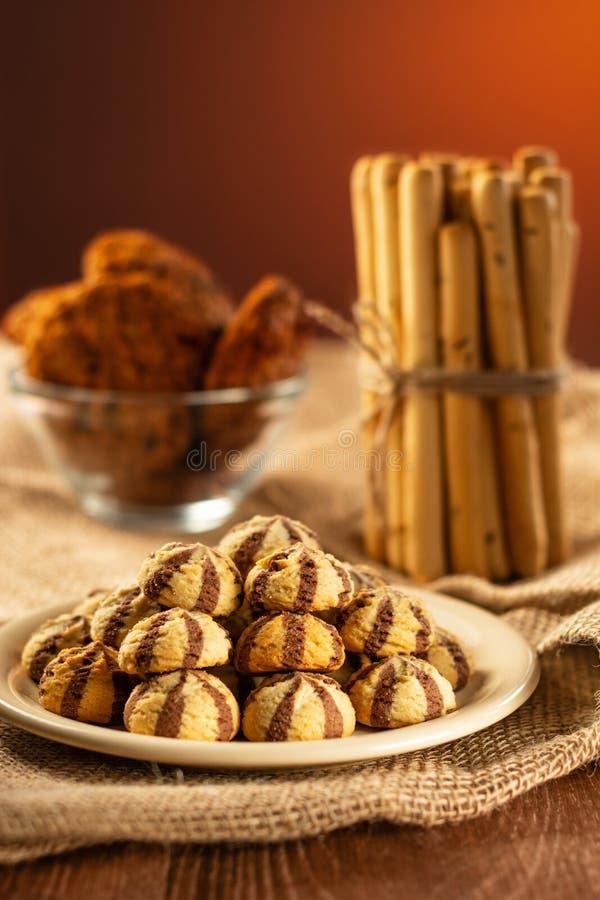 Un puñado de galletas en una placa, los breadsticks y las galletas de harina de avena fotos de archivo