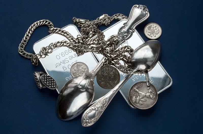 Un puñado de lingote de plata, de cubiertos, de joyería y de monedas de plata viejas en un fondo azul marino foto de archivo libre de regalías