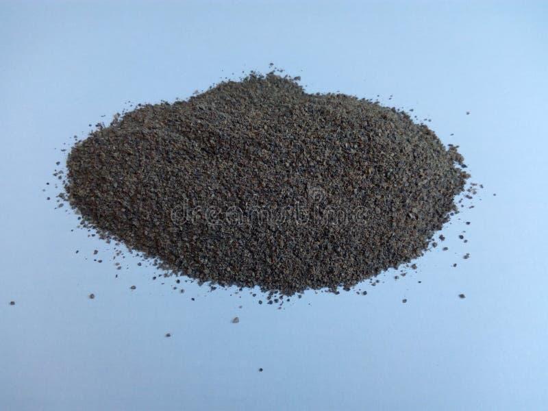 Un puñado de pimienta negra en un fondo blanco foto de archivo