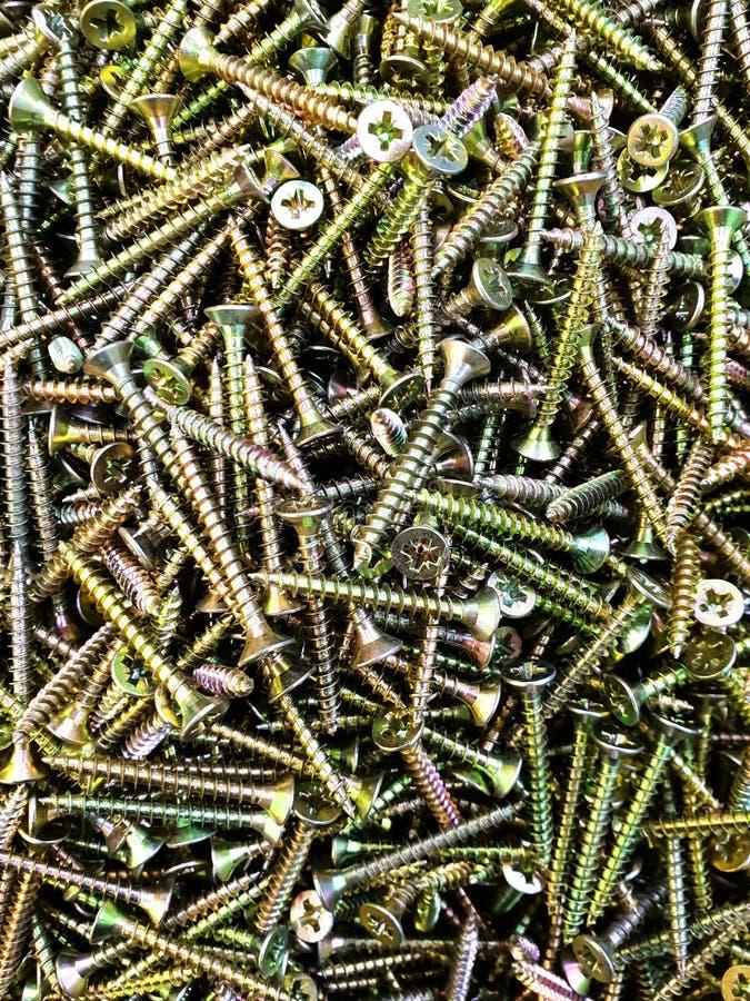 Un puñado de tornillos y de clavos del oro foto de archivo
