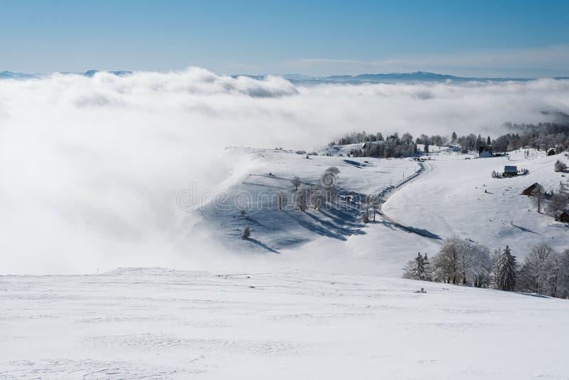 Un pueblo encima de la montaña cubierta con nieve y niebla fotos de archivo