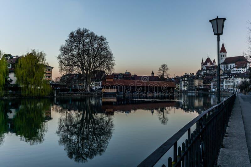 Un puente de madera que cruza el río Aare con el castillo de Thun en el fondo temprano por la mañana imágenes de archivo libres de regalías