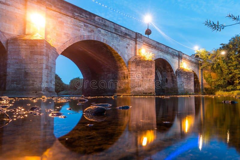 Un puente de piedra viejo del río con las luces foto de archivo