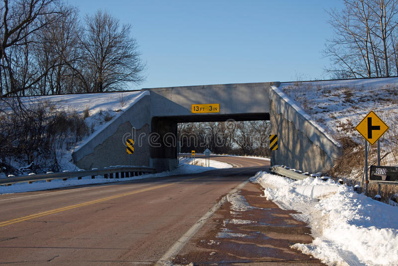 Un puente del ferrocarril sobre una carretera rural imagenes de archivo