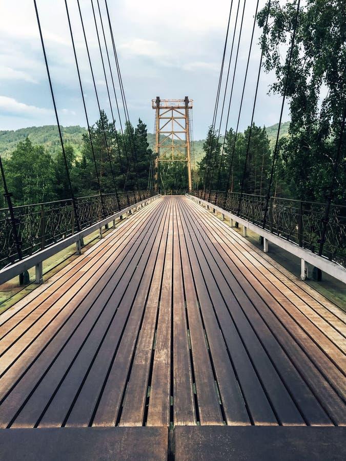 Un puente largo grande con una cubierta de madera del camino Rastros oscuros de uso fotografía de archivo
