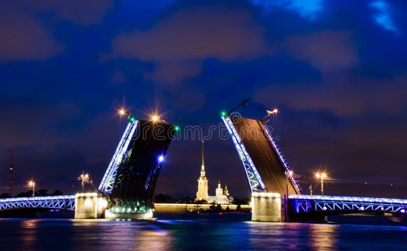 Un puente levadizo de St Petersburg en la noche con una fortaleza entre ella fotos de archivo