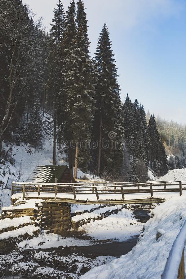 Un puente sobre una pequeña cala, invierno en el pueblo, la tierra debajo de la nieve fotografía de archivo