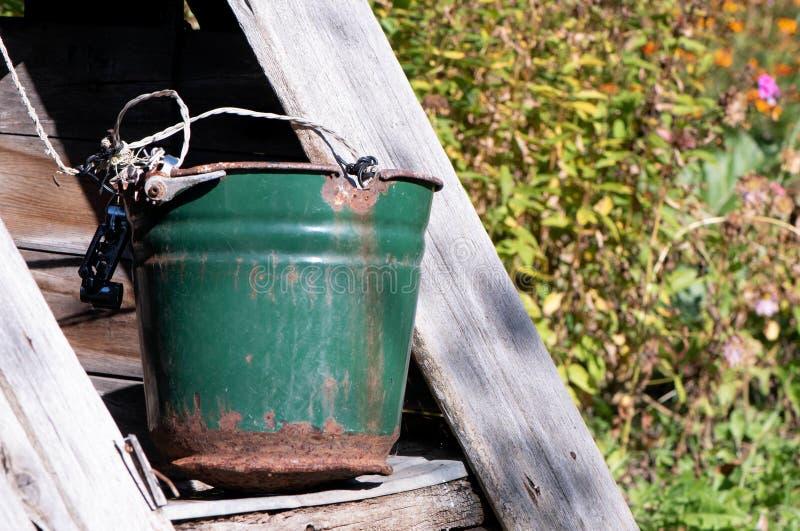 Un puits antique avec un seau dans un village européen photo stock