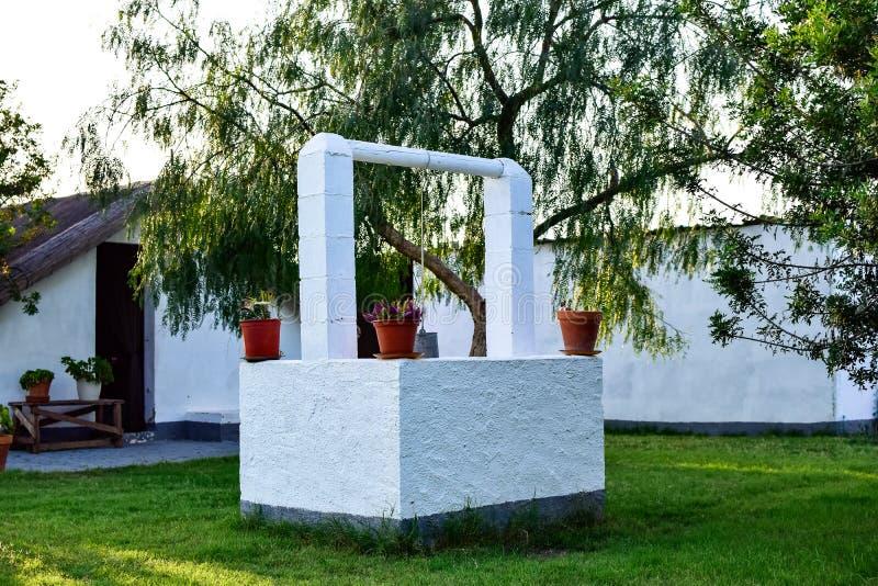 Un puits décoré des pots et des fleurs au milieu d'un jardin extérieur photographie stock libre de droits