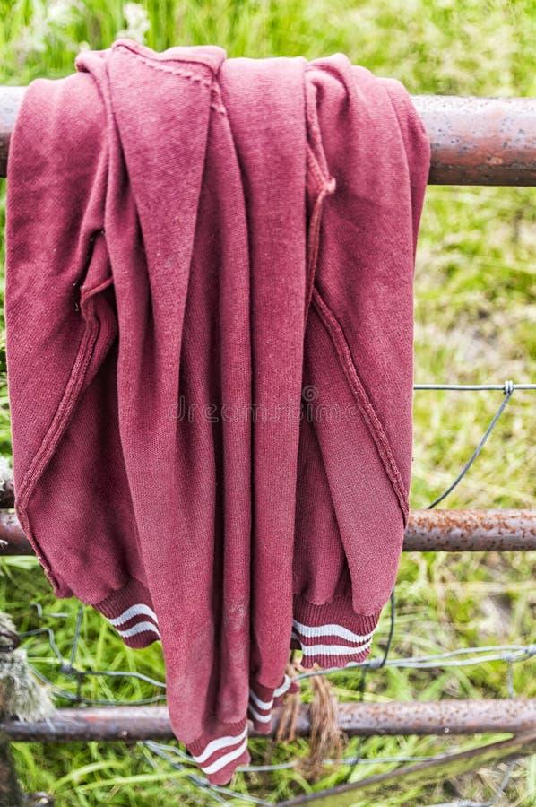 Un pull molletonné rouge accrochant au-dessus d'une barrière en acier images libres de droits