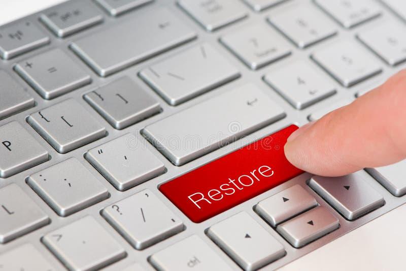 Un pulsante di ripristino rosso della stampa del dito sulla tastiera del computer portatile immagine stock libera da diritti