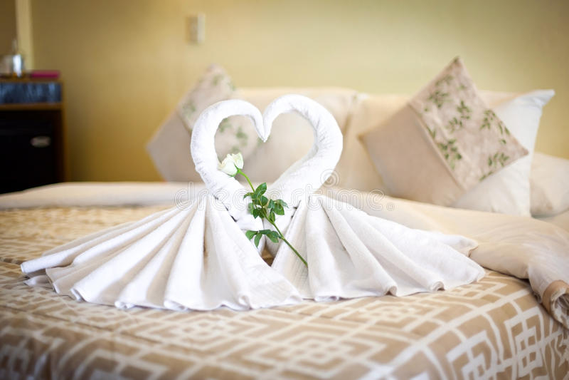 Un punto di vista di due cigni bianchi degli asciugamani sul lenzuolo in hotel fotografia stock libera da diritti