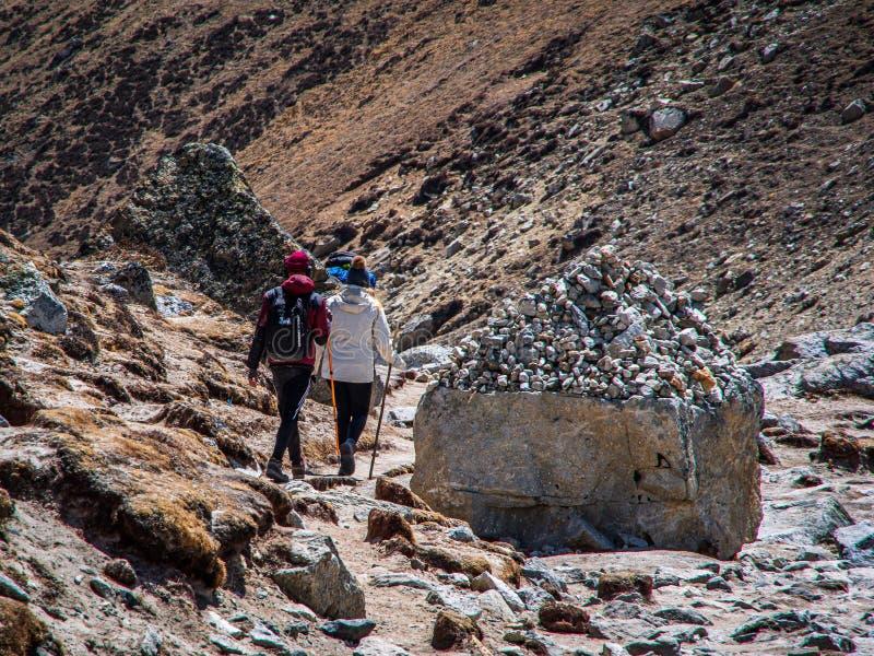Un punto di vista di Landcape di due viandanti sul percorso al campo base di everest fotografia stock libera da diritti