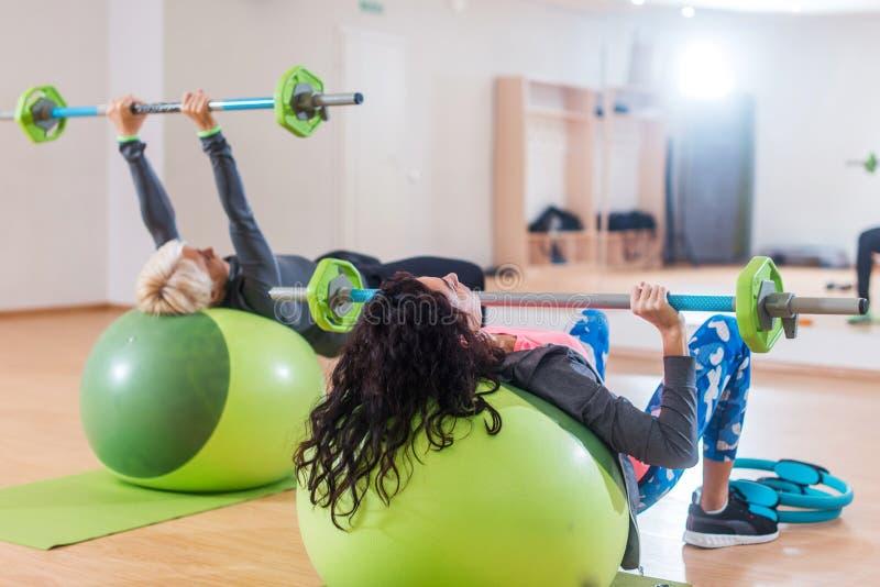 Un punto di vista posteriore di due donne che sollevano bilanciere che si trova sulla palla di stabilità mentre esercitandosi nel immagini stock