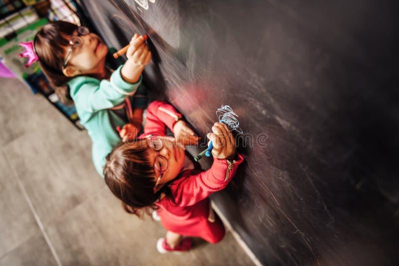 Un punto di vista superiore di due bambini soleggiati che indossano i vetri che attingono lavagna fotografia stock libera da diritti