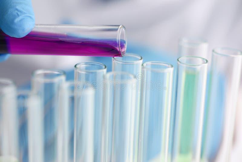 Un químico de sexo masculino sostiene el tubo de ensayo de vidrio foto de archivo
