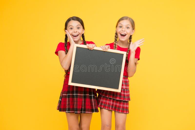Un qu? grandes noticias niños que presentan el tablón de anuncios Ventas grandes pequeñas muchachas felices con la pizarra Lugar  fotos de archivo