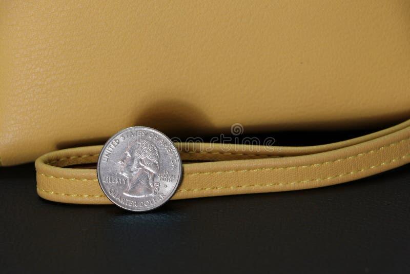 Un quart de pièces de monnaie de dollar US sur USD correspondant avec le portefeuille de couleur de sable sur le plancher noir photographie stock libre de droits