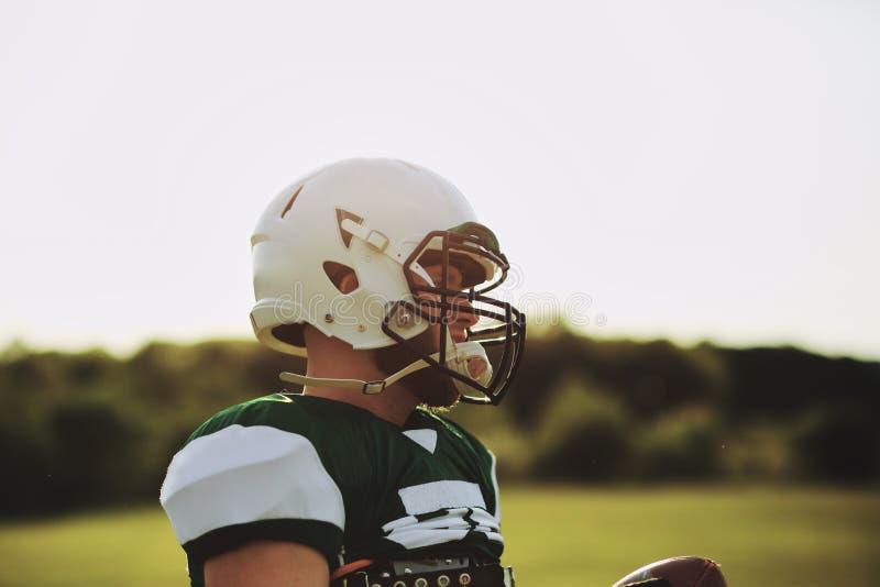 Un quarterback di calcio in un campo sportivo che regge una palla immagini stock