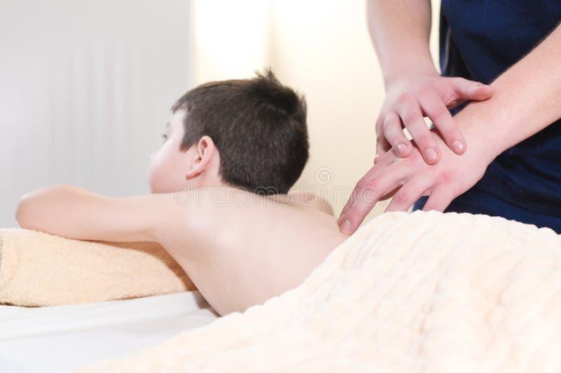 Un quiropr?ctico profesional da masajes a un ni?o peque?o Procedimiento del masaje de la salud fotografía de archivo libre de regalías