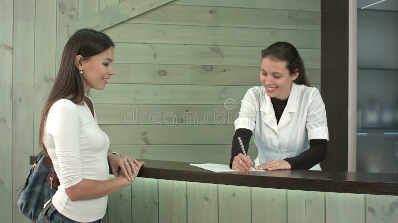 Un réceptionniste de station thermale saluant un client féminin au