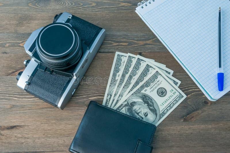 Un rétro appareil-photo, une bourse avec l'argent et un carnet avec un stylo sur une table en bois images libres de droits