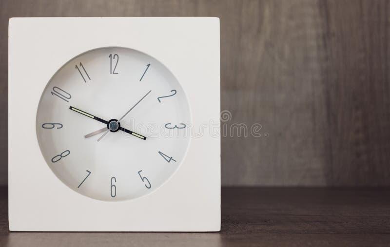 Un réveil avec la pièce à côté de elle pour le texte sur une armoire en bois photos libres de droits