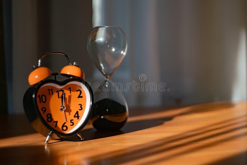 Un réveil orange est sur la table Il montre le temps de dîner photo stock