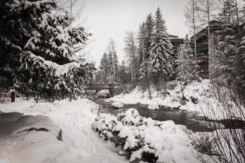 Un río rodeado por la nieve en Vail, Colorado durante invierno imagenes de archivo