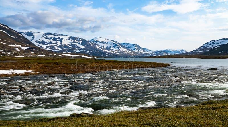Un río salvaje ártico que fluye de un lago en montañas nevosas imagen de archivo