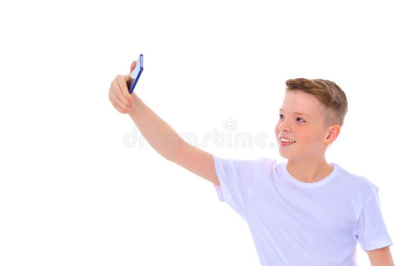 Un ragazzino allegro sta facendo un selfie immagine stock libera da diritti