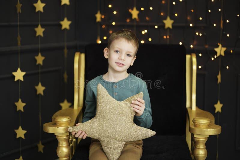 Un ragazzino bello si siede in una sedia che abbraccia un cuscino a forma di stella in un interno con le stelle dorate sul nero fotografie stock
