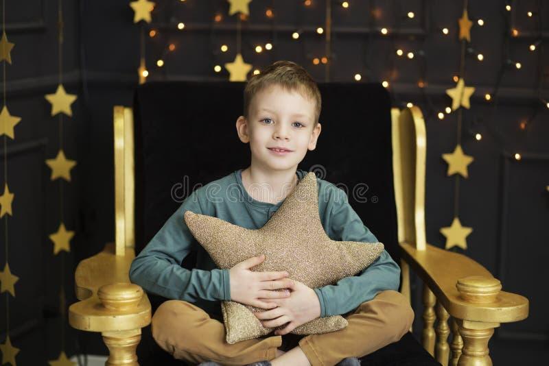 Un ragazzino bello si siede in una sedia che abbraccia un cuscino a forma di stella in un interno con le stelle dorate sul nero immagini stock