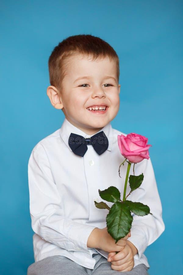 Un ragazzino bello sta tenendo una rosa rosa fotografia stock