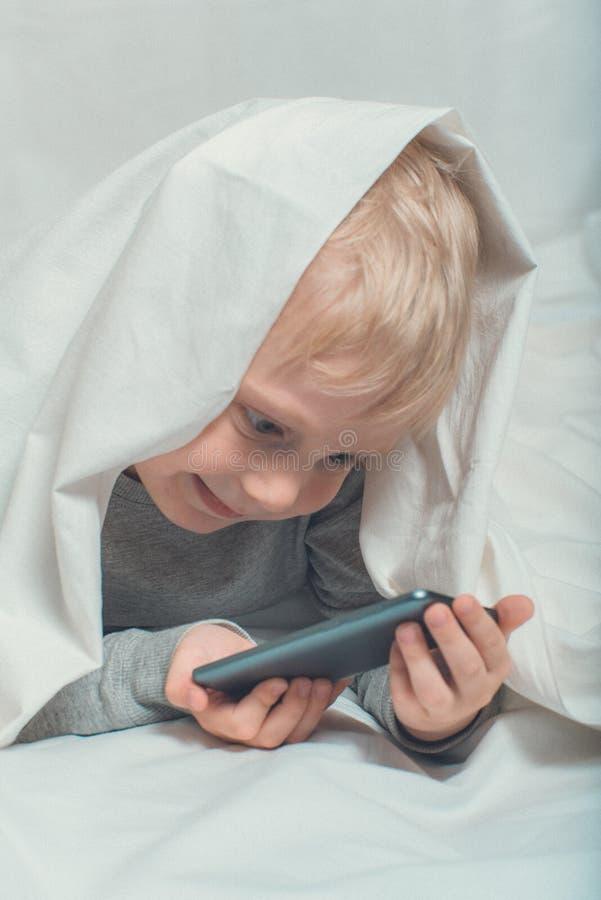 Un ragazzino biondo sta guardando qualcosa su uno smartphone Morire nel letto e nascondersi sotto le coperte Gadget Leisure immagini stock libere da diritti