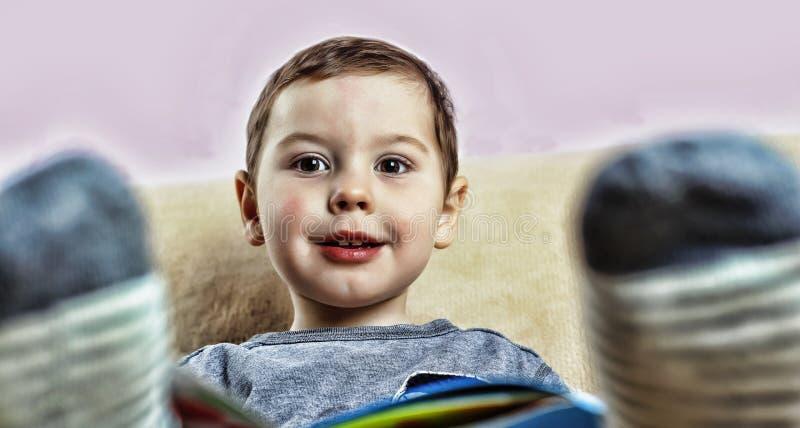 Un ragazzino che legge un libro mentre sedendosi sullo strato a casa fotografie stock libere da diritti