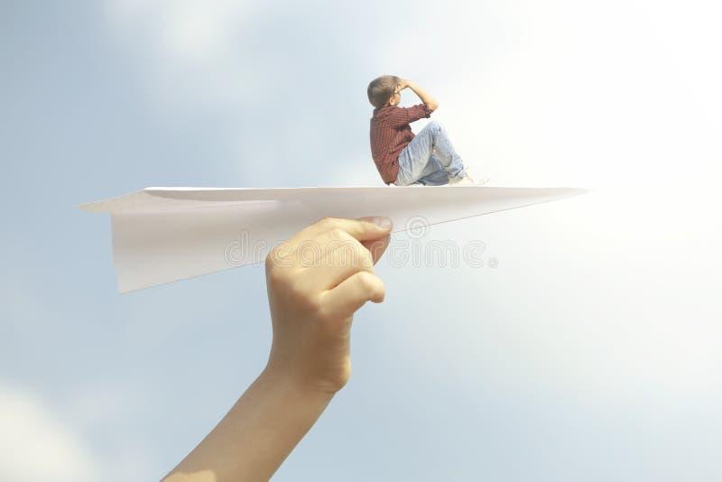 un ragazzino che vola liberamente sopra un aeroplano di carta fotografia stock libera da diritti