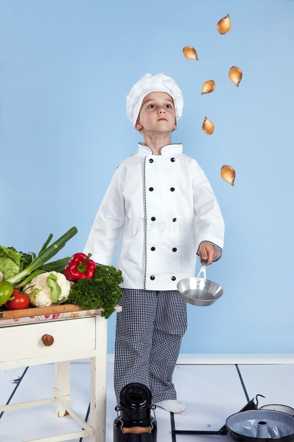 Un ragazzino come cuoco del cuoco unico che produce insalata immagini stock