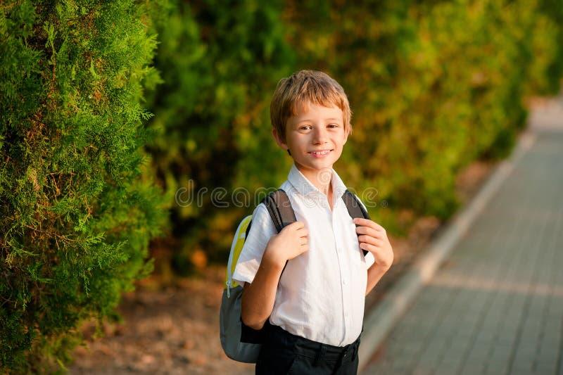 Un ragazzino con uno zaino va sul suo modo alla scuola fotografia stock libera da diritti