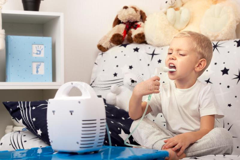 Un ragazzino fa l'inalazione con un nebulizzatore fotografia stock libera da diritti