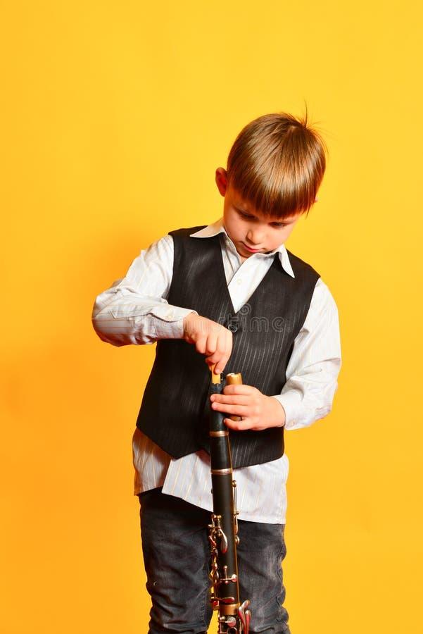 Un ragazzino nelle arie del costume il clarinetto prima del gioco della scena di musica fotografia stock libera da diritti