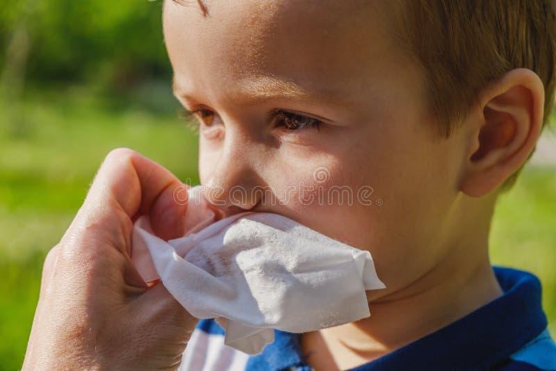 Un ragazzino sta mangiando un gelato in parco e pulisce la sua bocca con un tovagliolo fotografie stock libere da diritti