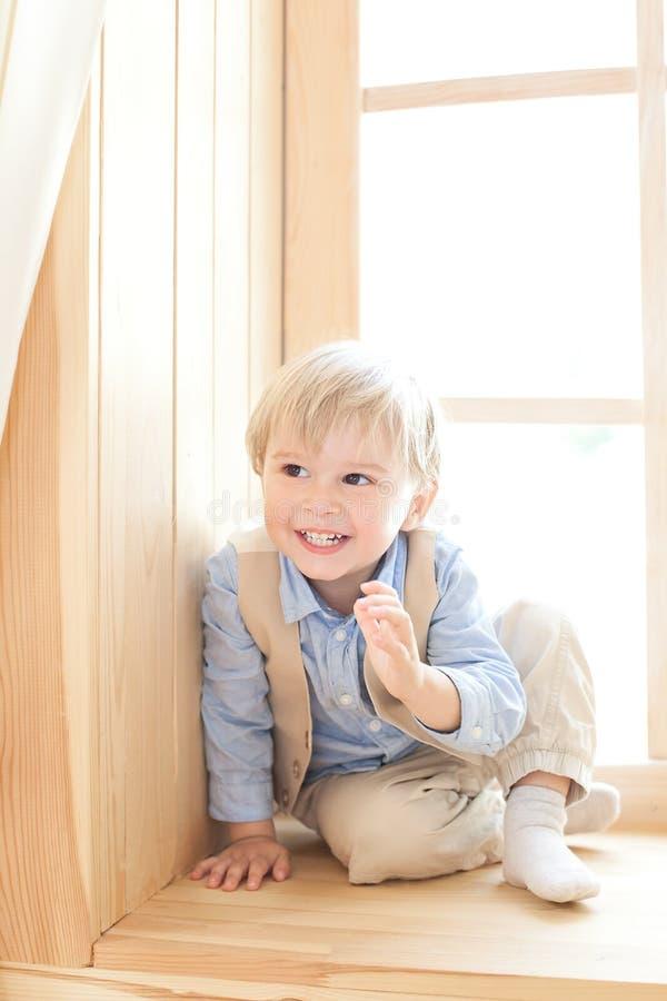 Un ragazzino sta sedendosi sul davanzale nella scuola materna Il concetto di svago, di svago, della gente e dello stile di vita R immagini stock