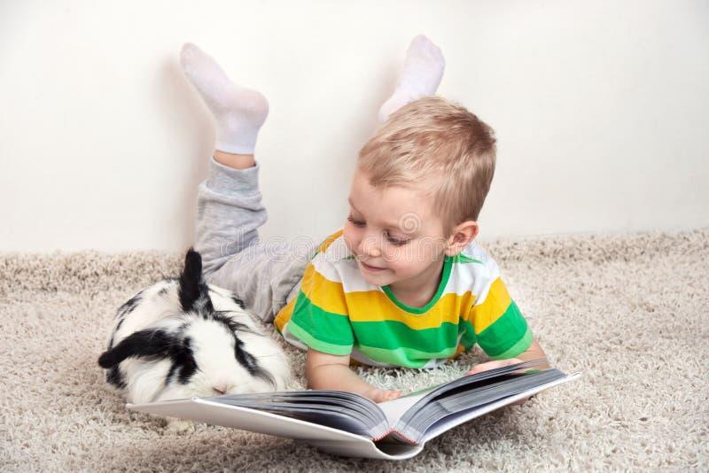 Un ragazzino sta trovandosi sul tappeto con il suo coniglio caro e legge un libro il suo animale domestico fotografia stock libera da diritti