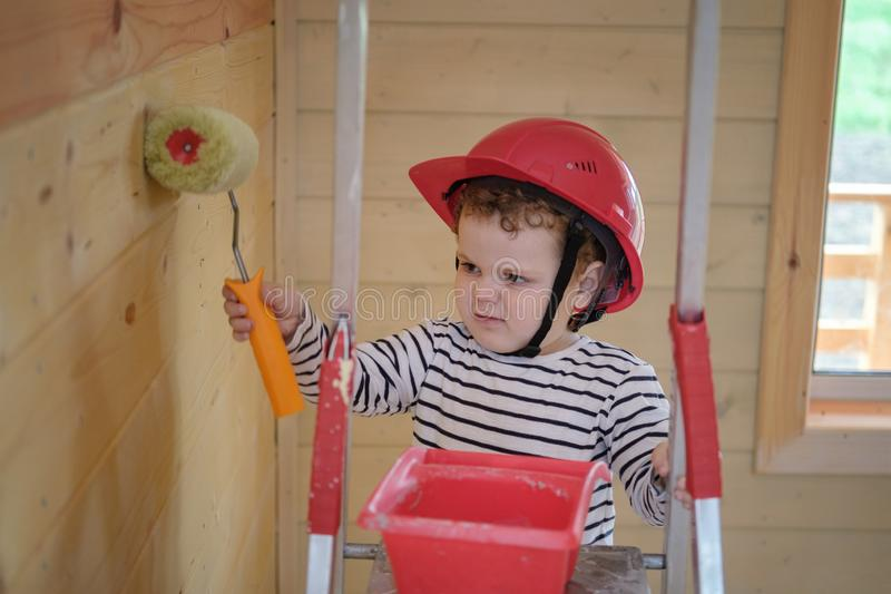 Un ragazzino sveglio in un casco protettivo dipinge la parete di una casa di legno con un rullo, stante su una scala a libro fotografia stock libera da diritti